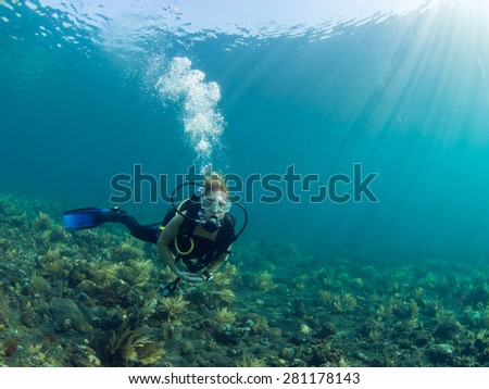 Female Scuba diver hovering over a coral reef at Tulamben, Bali Indonesia - stock photo