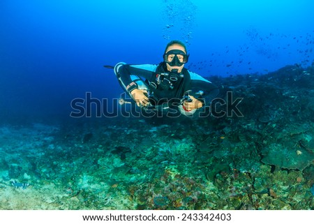 Female SCUBA diver using a techical side mount system on a deep coral reef - stock photo