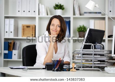 Female secretary sitting on chair at her office - stock photo