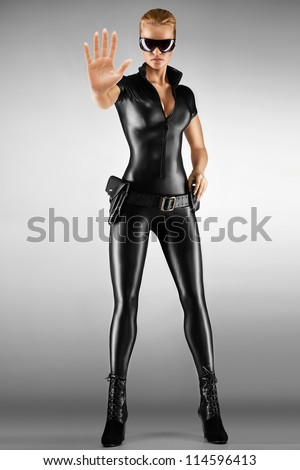 Female security guard in tight, black, sexy outfit with pistol. - stock photo