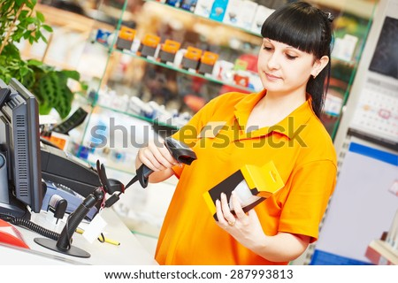 female seller with bar code scanner scanning lamp at store - stock photo