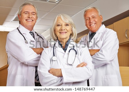 Female senior doctor and medical team with their arms crossed in a hospital - stock photo