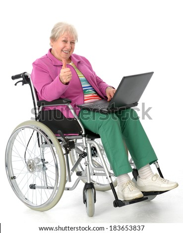 female senior in wheelchair using a computer  - stock photo