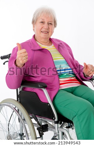 female senior in wheelchair with thumb up  - stock photo