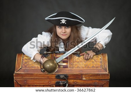 Female sexy pirate with chest of treasure and saber on black background. - stock photo