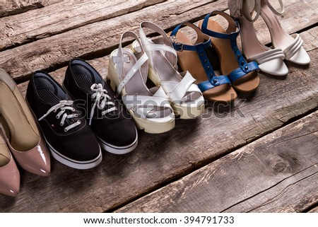 Female shoes on old floor. Tankette shoes and fabric keds. Footwear for every taste. From simplicity to luxury. - stock photo