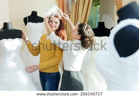 Female shop consultant helps girl chooses white bridal outfit at shop of wedding fashion - stock photo