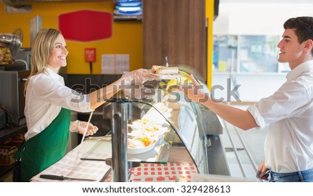 Female shop owner serving sandwich to male customer in bakery - stock photo