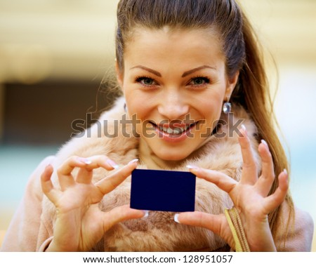 Female shopper holding a credit card with shopping bags - stock photo