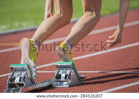 Female short track runner starts out of the blocks. - stock photo