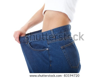 female shows her old huge pair of jeans, weight loss concept, studio shoot, - stock photo