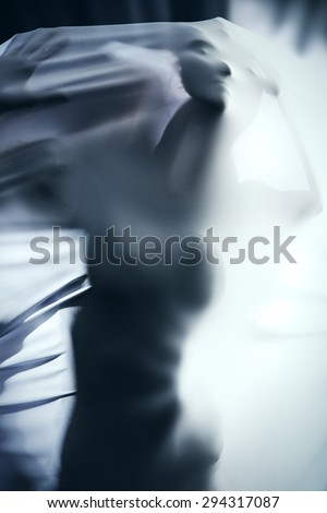 Female silhouette breaking through the white fabric over black background. Art project, theater. Modern dance. - stock photo