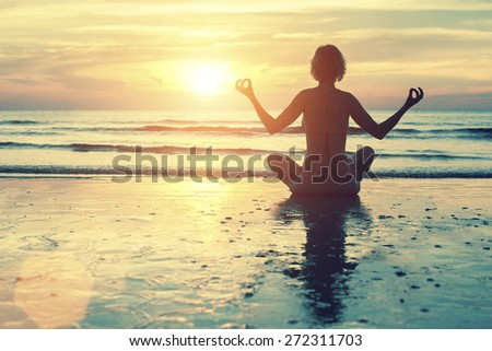 Female silhouette in yoga meditation pose at amazing sunset on the sea. - stock photo