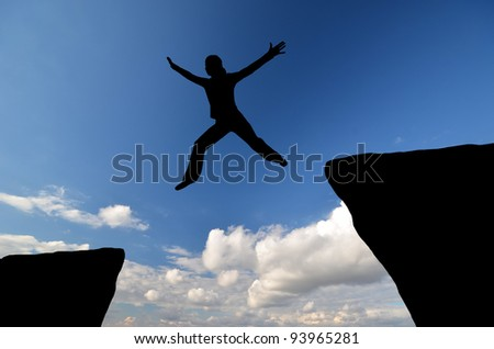 female silhouette jumping from one rock to another in the sky - stock photo