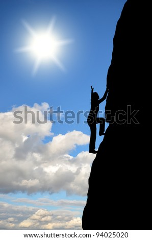 female silhouette wins the top of the rock in the sky - stock photo
