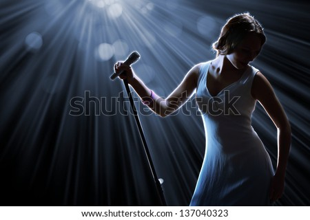 Female singer on the stage holding a microphone - stock photo