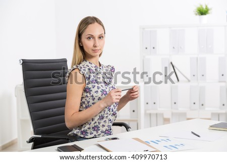 Female sitting at white office desk with shelves in the background - stock photo