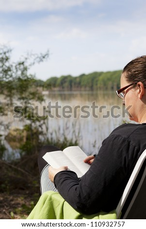 Female sitting in a chair reading a book with a lake in front of her. A boat is sailing on the lake. Focus is on the boat. - stock photo