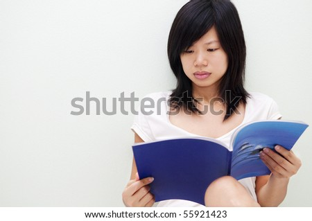 Female sitting on floor at home, reading book. - stock photo