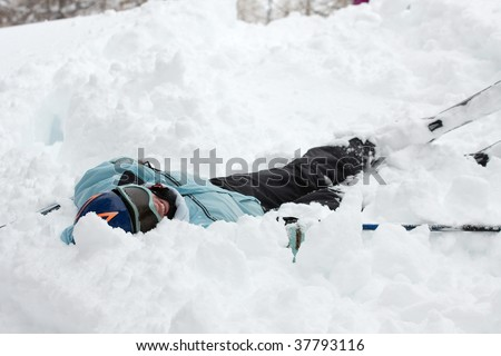 Female skier fallen into deep snow - stock photo