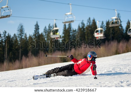 Female skier fell in snow during the descent from mountain at resort in sunny day against ski-lift, forest and blue sky. Woman is wearing red jacket, helmet and goggles. - stock photo