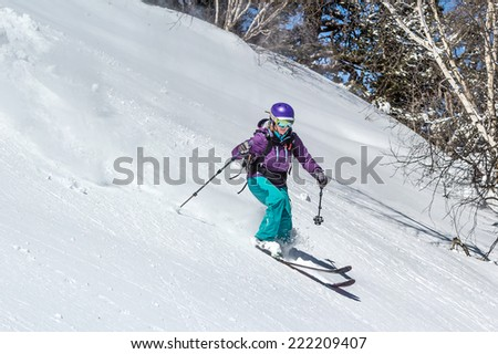 Female skier in deep snow. Off-piste skiing in soft snow on a cold sunny day in the forest zone - stock photo