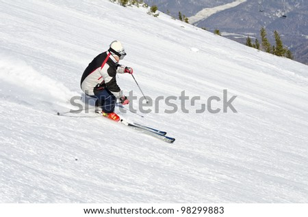 Female skier on the mountain side on a sunny day - stock photo
