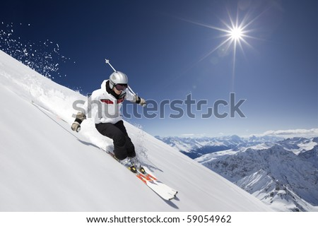 female skier skiing downhill with sun and mountains. - stock photo