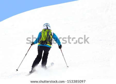 Female skier turning in deep powder with mountains valley's - stock photo