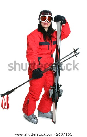 Female skier wearing a red ski suit and carryng matching skis and poles. - stock photo