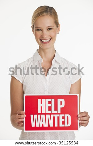 female small business owner holding up Help Wanted sign with white seamless background - stock photo