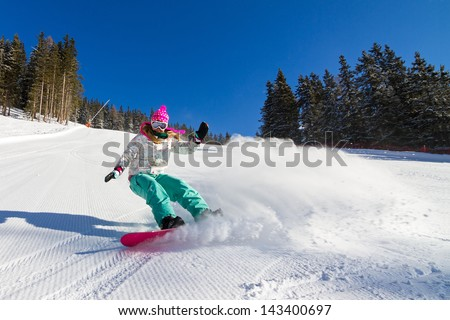 Female snowboarder on the slopes on a sunny morning in the Italian alps - stock photo