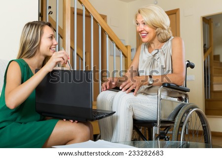 Female social worker with laptop questioning smiling handicapped aged woman. Focus on mature - stock photo