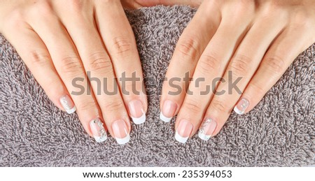 Female soft hands with beautiful french manicure on the towel - stock photo