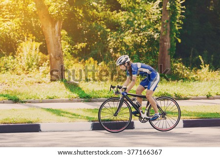 Female sportsman cyclist riding racing bicycle. Woman cycling on countryside summer sunny road or highway. Training for triathlon or cycling competition. - stock photo
