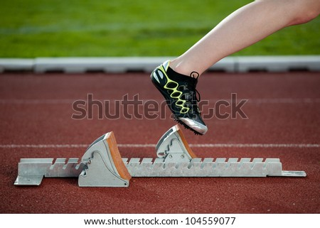 Female sprinter leaving the starting blocks for a sprint run on a track - stock photo