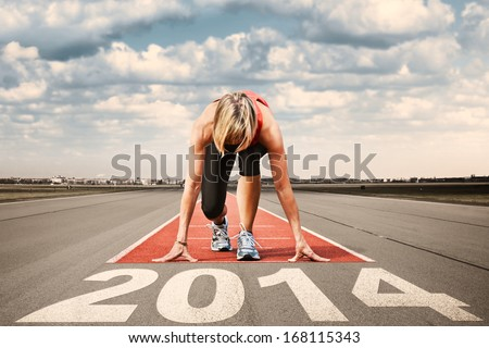 Female sprinter prepares for the start on an airport runway.In the foreground perspective view of  letters 2014. - stock photo
