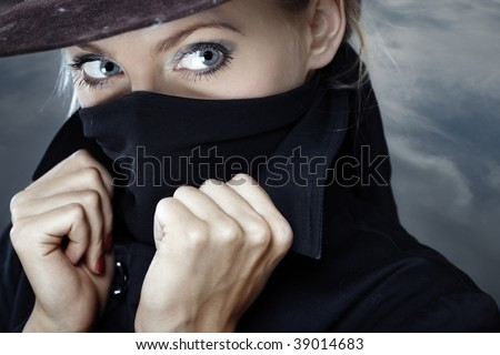 Female spy in hat with face covered by the coat collar - stock photo