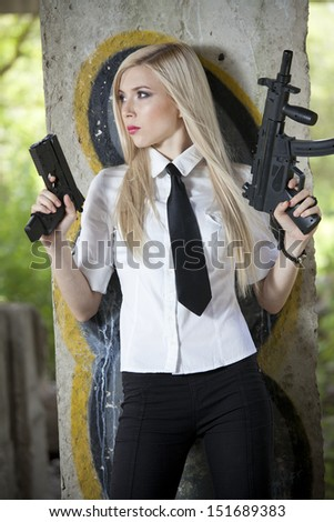 female spy in shirt and tie with two guns standing at the wall - stock photo