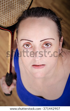 Female squash player holding racket in sports gym. - stock photo