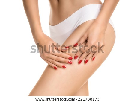 Female squeezing buttock and showing no cellulite in her perfectly shaped body. Isolated on white. - stock photo