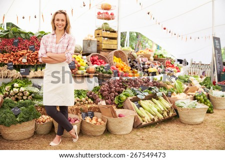 Female Stall Holder At Farmers Fresh Food Market - stock photo