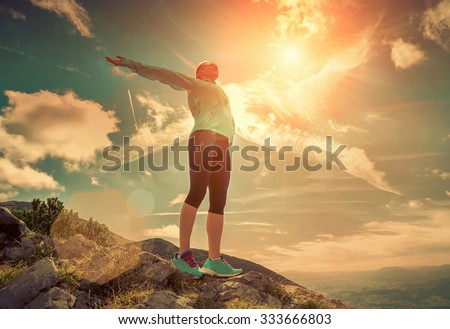 Female stay on the top of mountain under sunlight. - stock photo