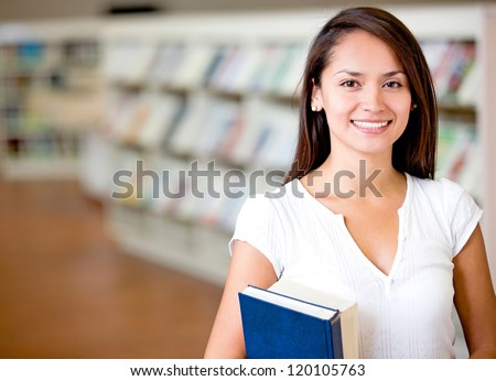 Female student at the library looking happy - stock photo