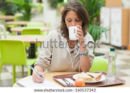 Female student doing homework while having breakfast in the cafeteria - stock photo