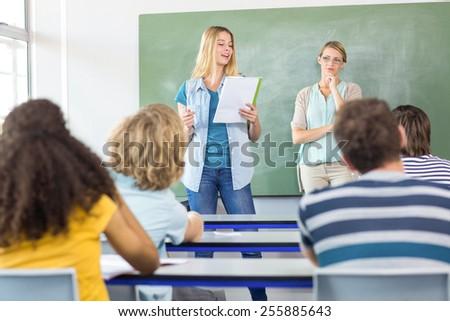 Female student explaining notes besides teacher in the class - stock photo