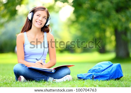 Female student girl outside in park listening to music on headphones while studying. Happy young university student of mixed Asian and Caucasian ethnicity. - stock photo