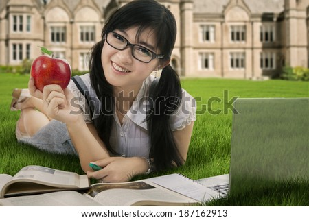 Female student holding a red apple while studying at the park - stock photo