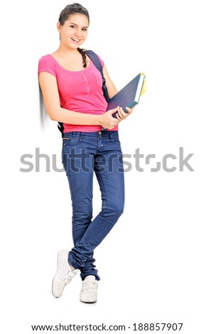 Female student holding books and leaning against a wall isolated on white background - stock photo