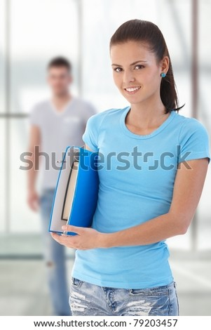 Female student holding folder, looking at camera, friend in background.? - stock photo